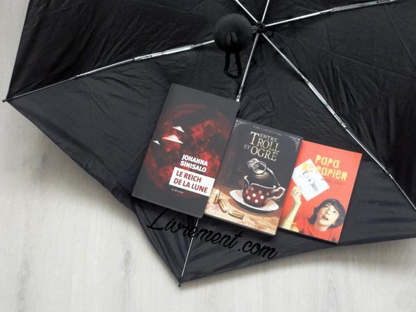 Trois romans acquis en avril 2018, pris en photo dans un parapluie retourné, par le blog Livrement