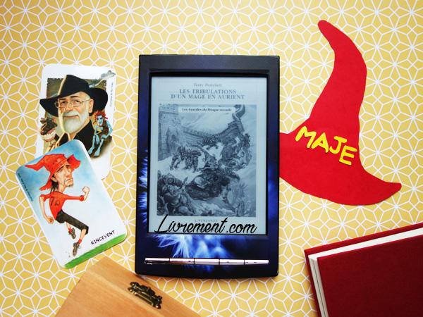 """Mise en scène du roman """"Les tribulations d'un mage en Aurient"""" de Terry Pratchett : bagage, cartes représentant Rincevent et Terry Pratchett, chapeau de Rincevent où il est marqué """"maje"""" et livre à la couverture rouge"""