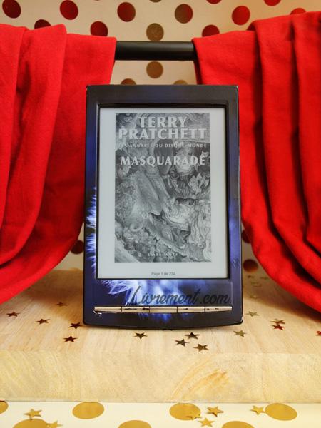 """Mise en scène du roman """"Masquarade"""" de Terry Pratchett : le livre se trouve au centre d'une scène de théâtre"""