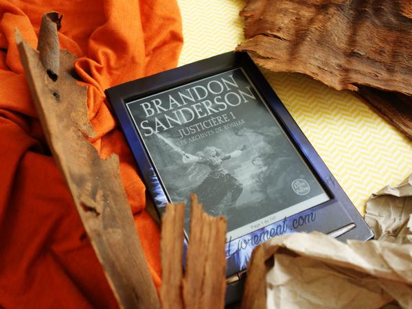 Mise en scène du roman Justicière de Brandon Sanderson : dans les tons de la couverture : marron, orange, jaune avec un tissu, du bois et des papiers