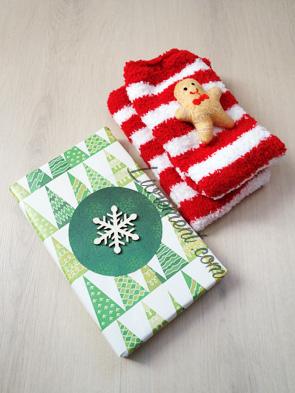 Colis surprise : un livre joliment emballé et des chaussettes rouges et blanches avec un pain d'épice cousu dessus