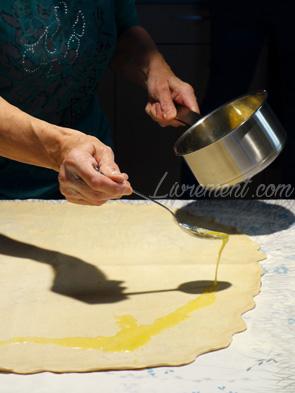 Préparation de la pâte à strudel : on verse du beurre liquide