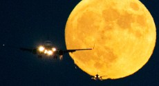 Landing jets lined up for an LAX runway on the evening of a full moon.