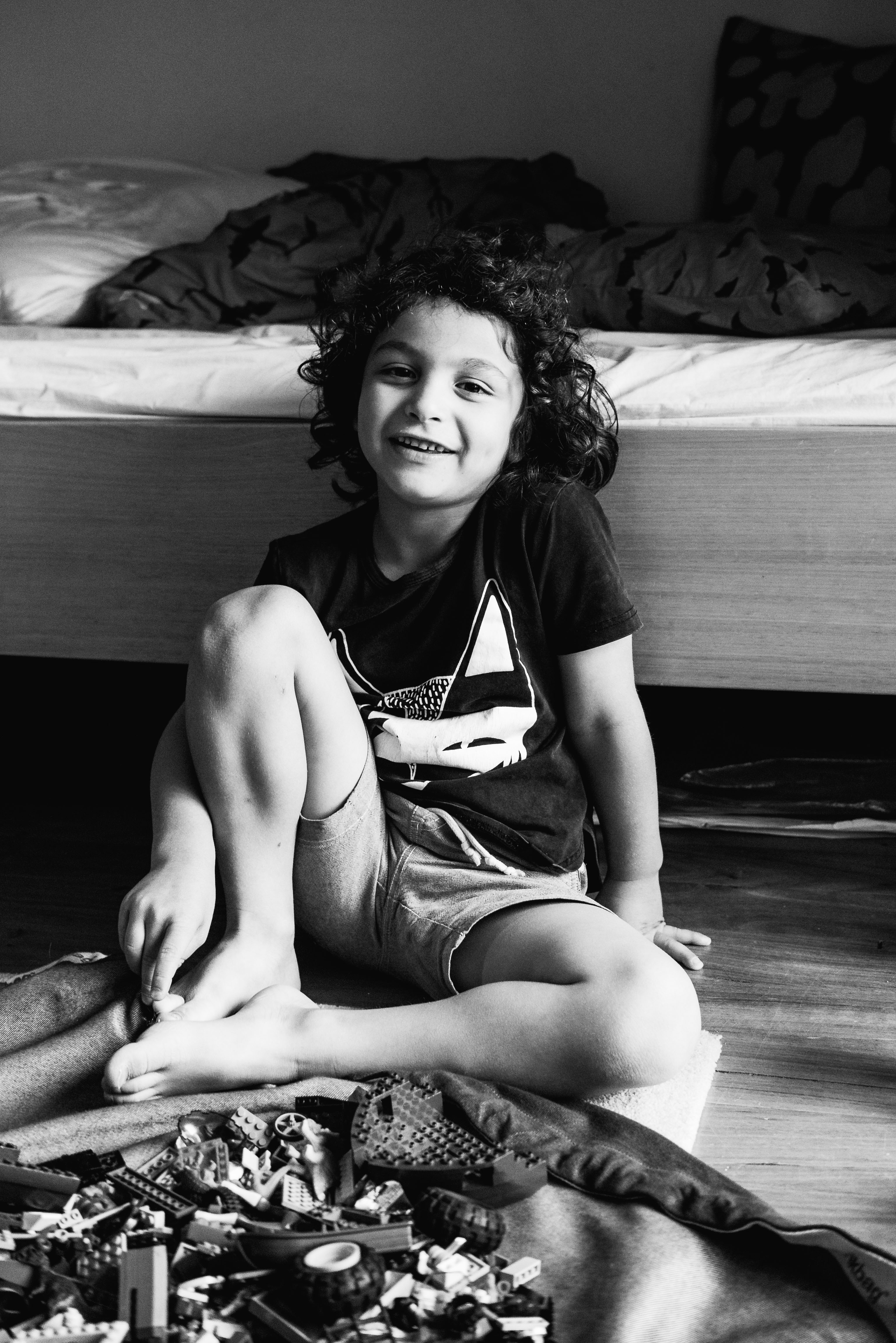 photograph of a boy smiling and sitting by his bed in Carlton North, Melbourne, Australia