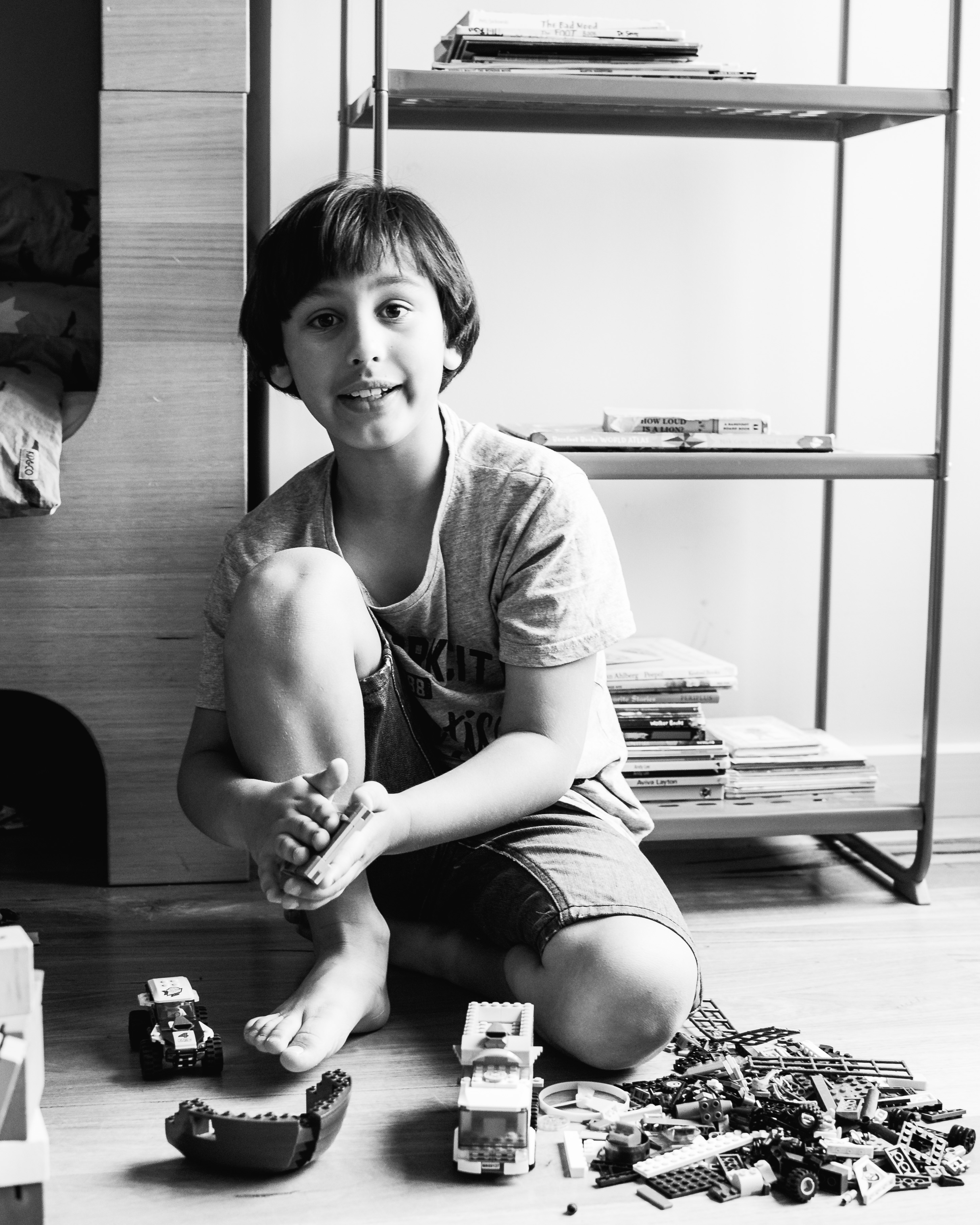 photograph of a boy talking while creating and building with Lego in his bedroom in Carlton North, Melbourne, Australia