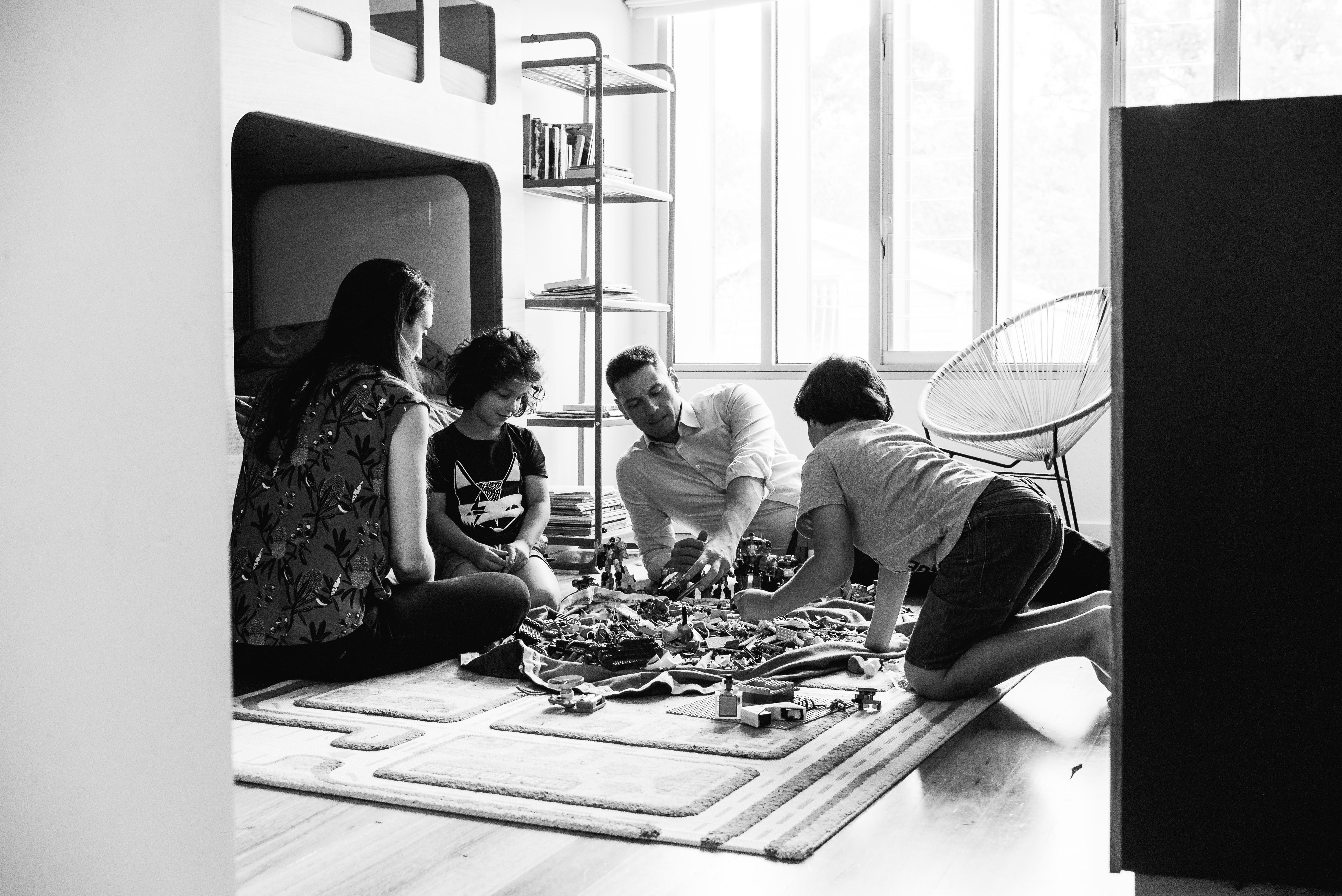 photograph of parents and their children creating and building with Lego in their bedroom in Carlton North, Melbourne, Australia