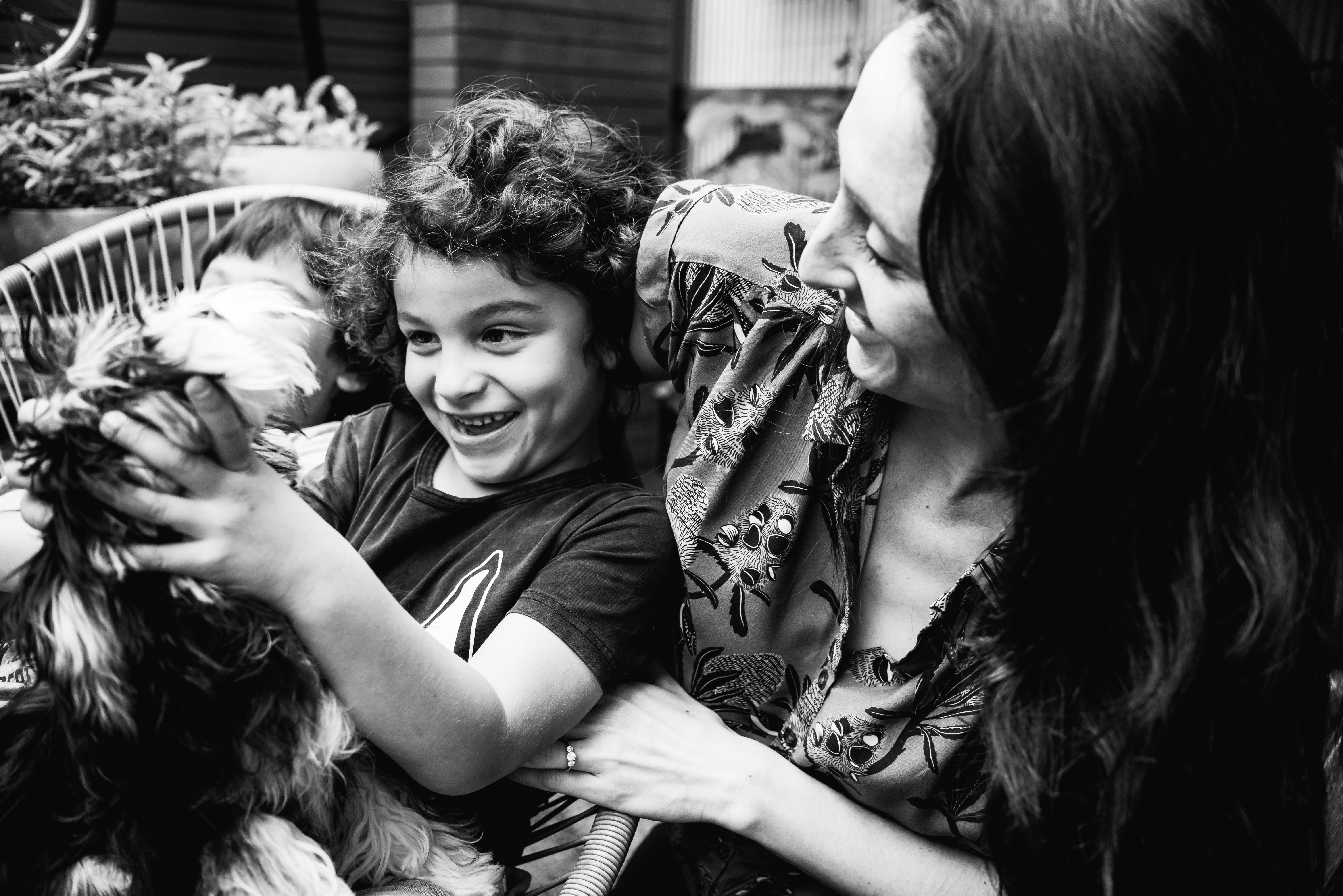 funny photograph of a boy holding his pet dog as his mother watches in Carlton North, Melbourne, Australia
