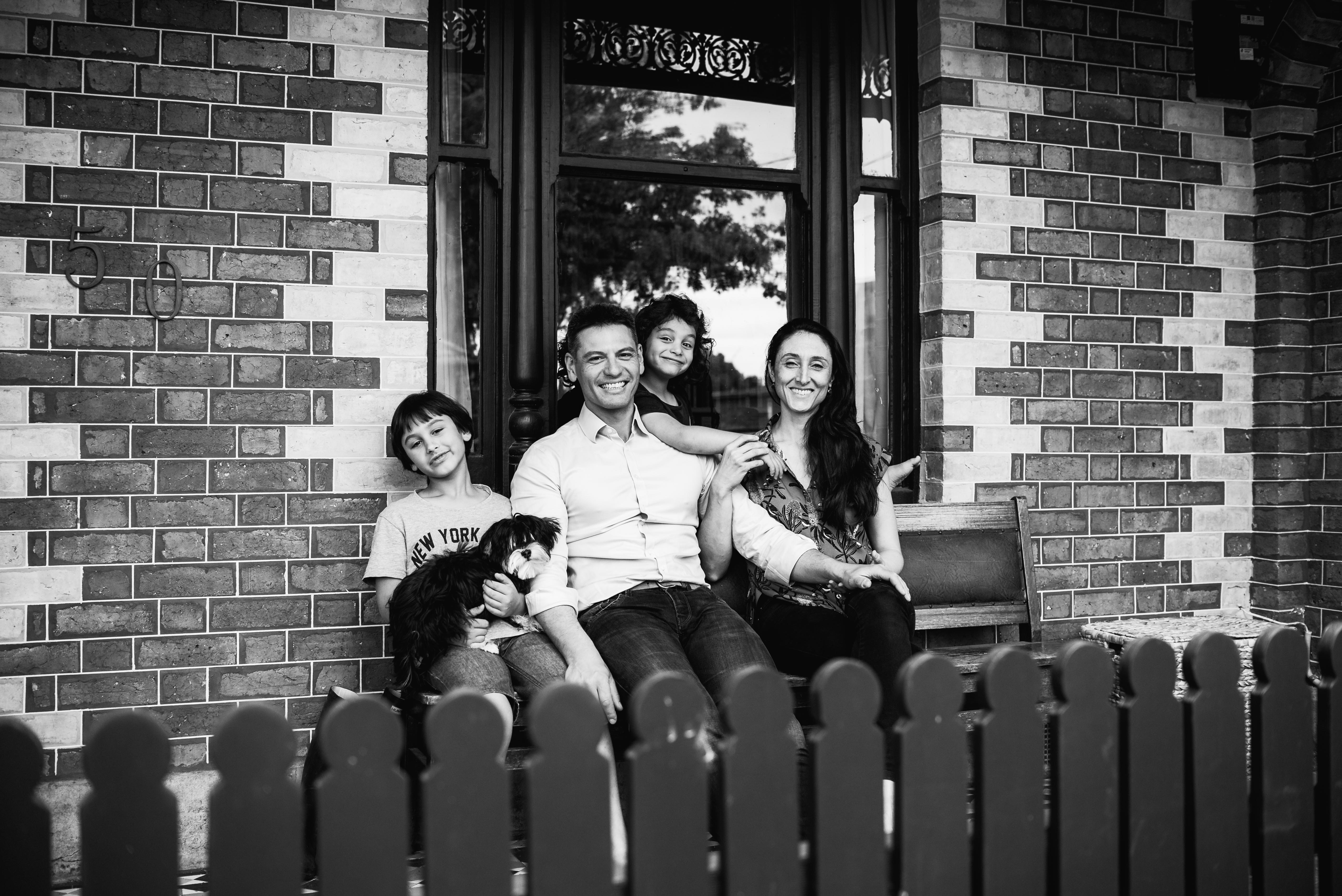 photograph of a family sitting at the front of their home in Carlton North, Melbourne, Australia