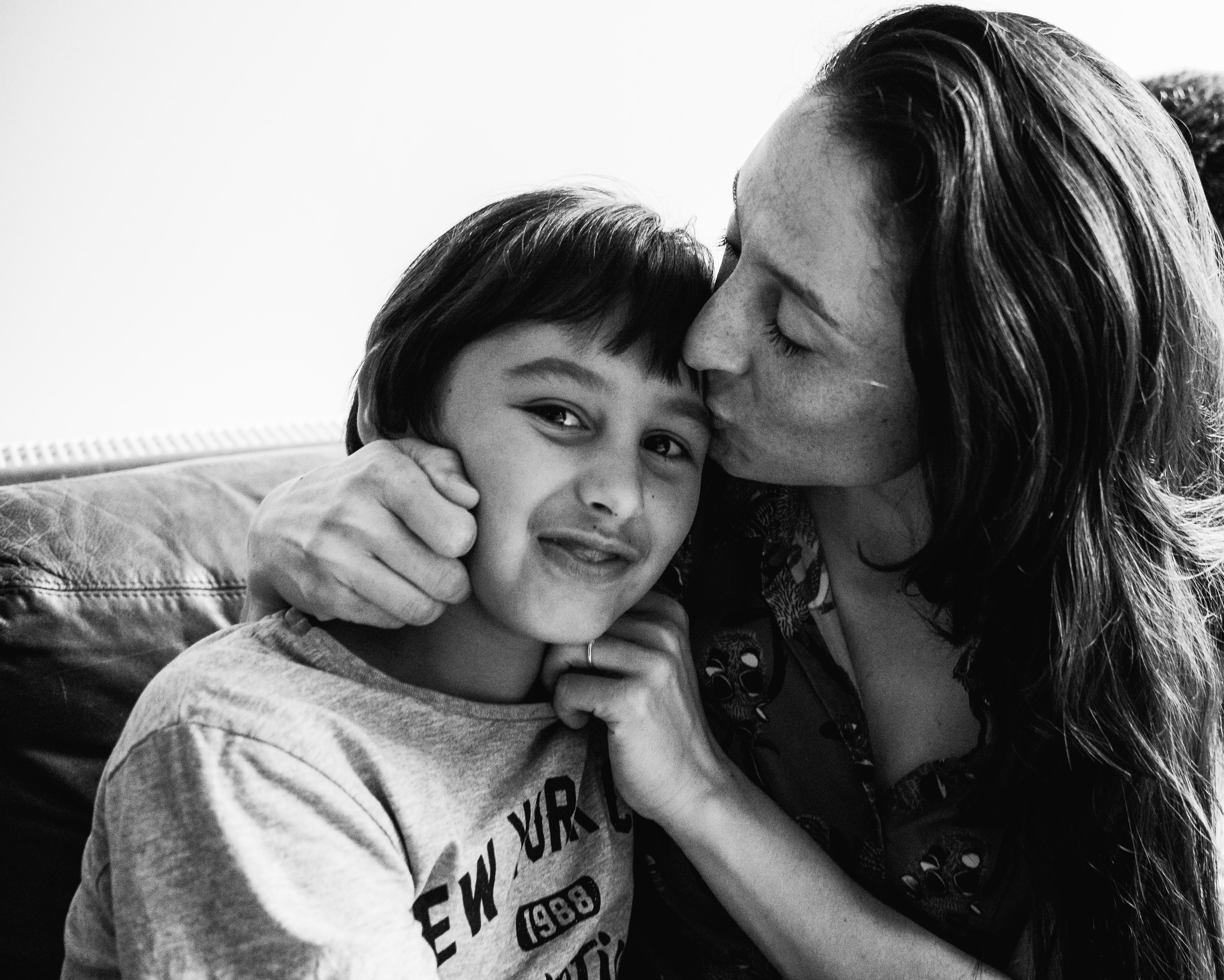 photograph of mother kissing and cuddling her son in Carlton North, Melbourne, Australia