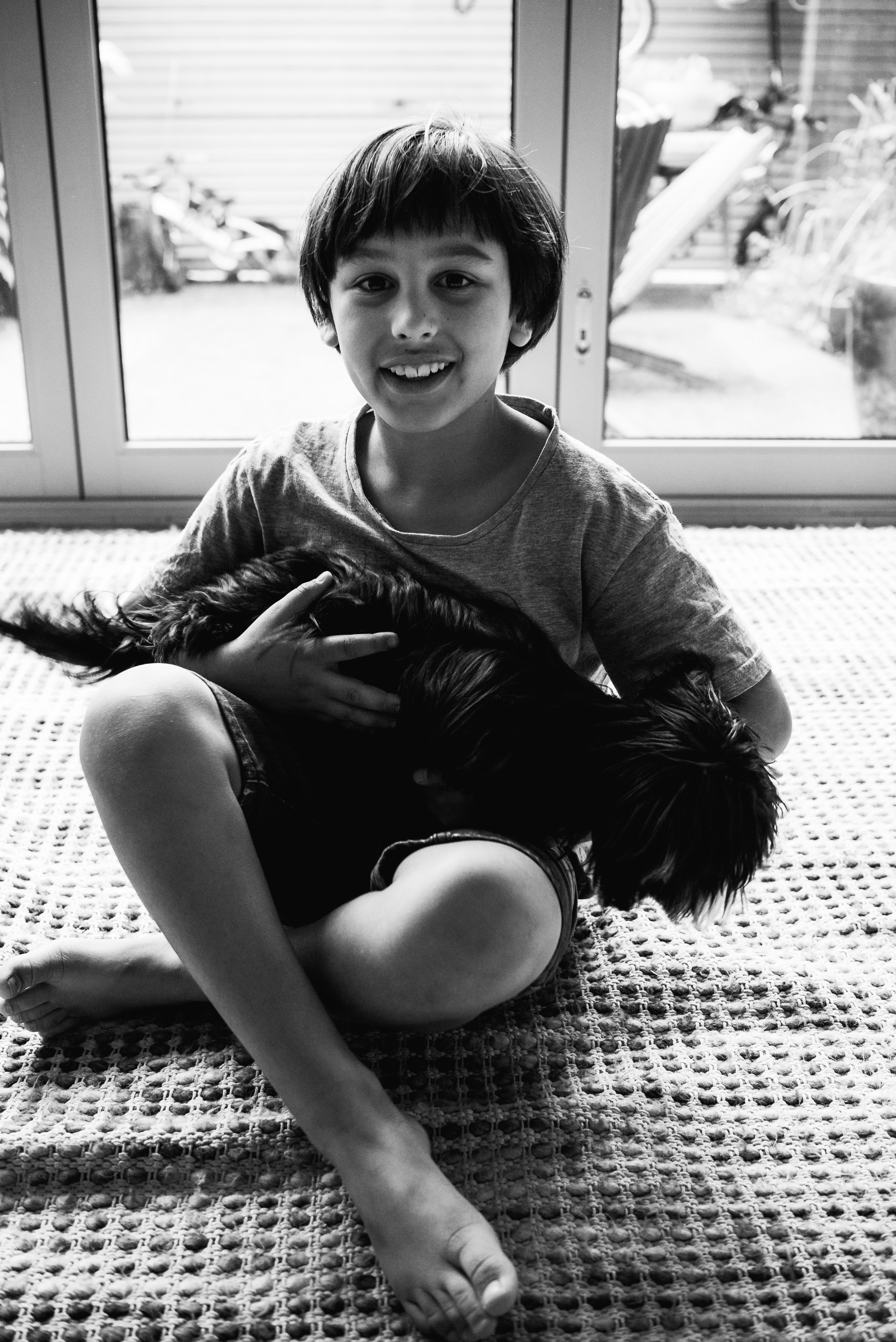 photograph of a boy and his cute dog cuddling in Carlton North, Melbourne, Australia