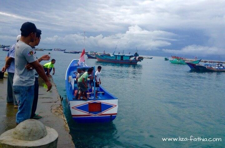 Nelayan sedang memarkir perahu boat di dermaga.