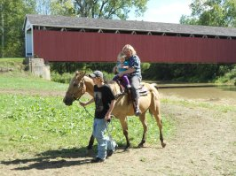 Emily and Maya on a horse at the Matthews Covered Bridge Festival