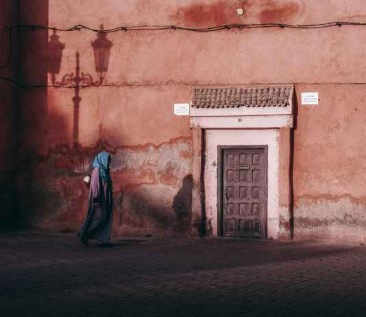 anonymous ethnic woman walking on pavement near old house
