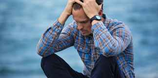 man in blue and brown plaid dress shirt touching his hair