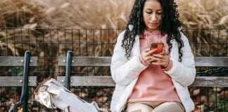 serious hispanic woman messaging on smartphone