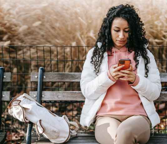 serious hispanic woman messaging on smartphone