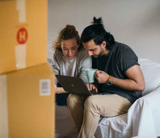 young multiethnic couple watching laptop while moving house