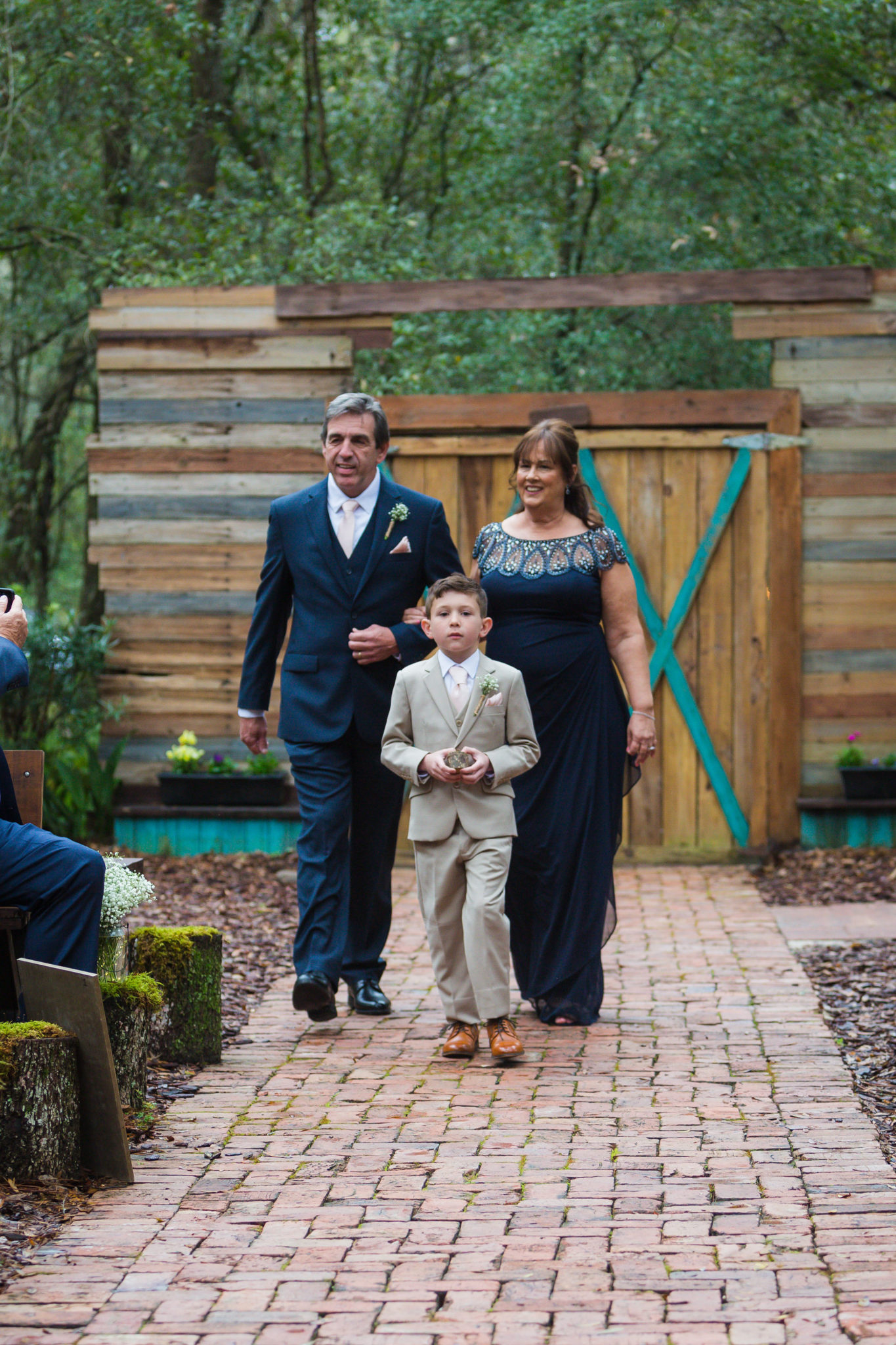 Mother and father of the groom walking down the aisle with the ringbearer and son of the groom.