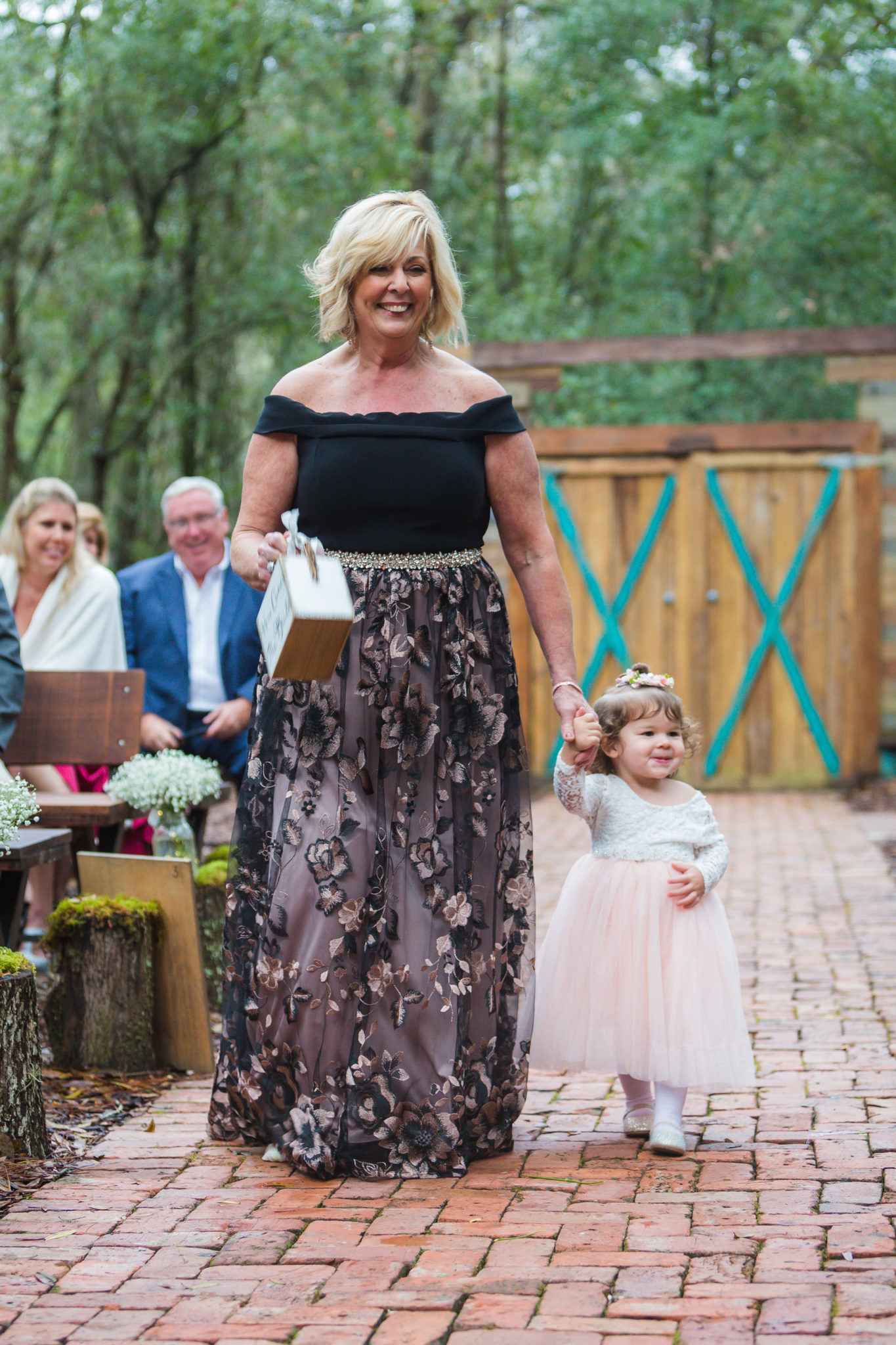 Mother of the bride walking down the aisle with the bride and groom's daughter and flower girl.