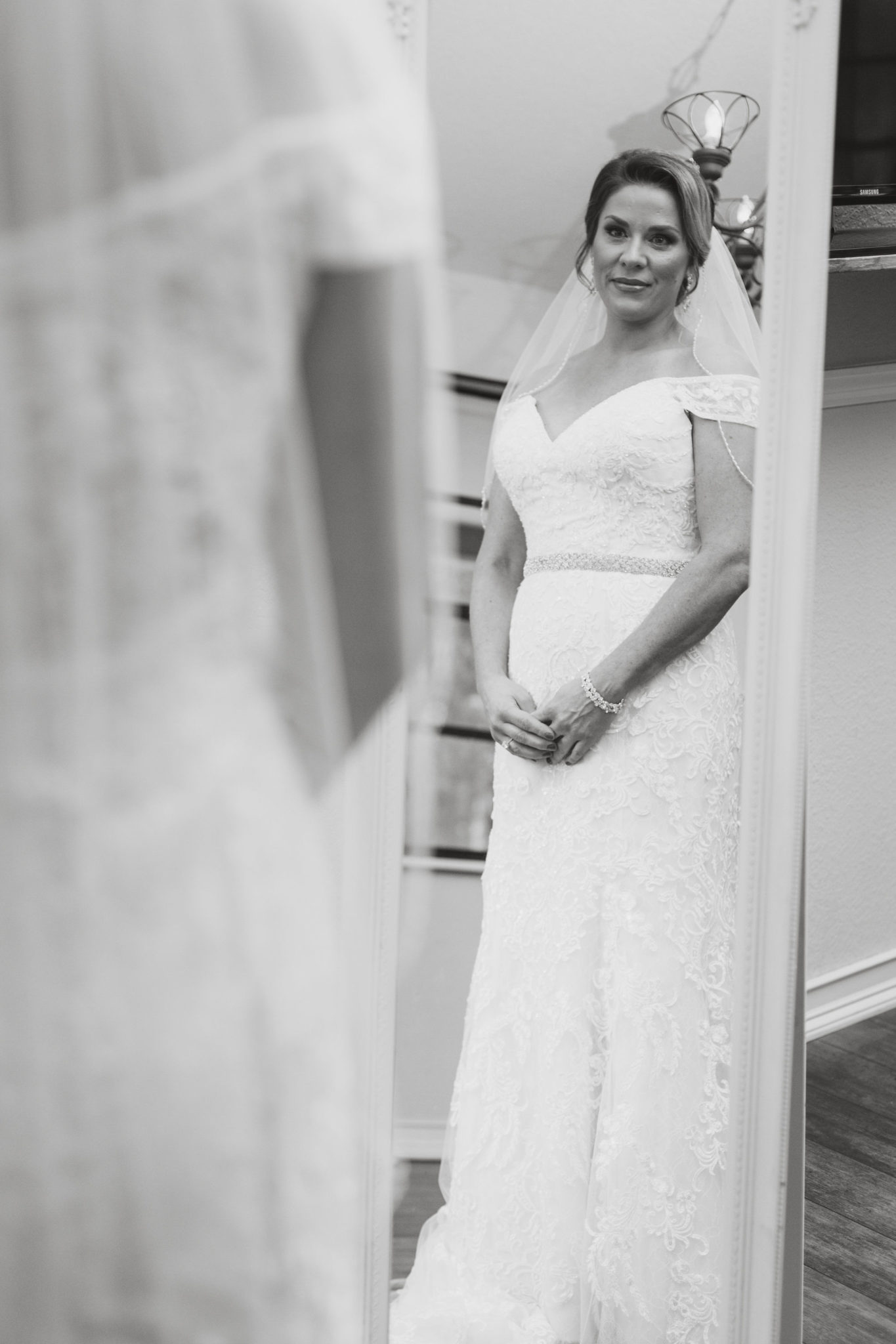 Bride looking at her reflection in the mirror.