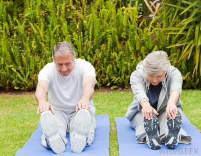 elderly-woman-and-man-on-yoga-mats-stretching