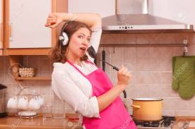 Cooking preparing and making food concept. Modern funny woman housewife cook chef wearing pink apron and listening music on earphones standing in kitchen.