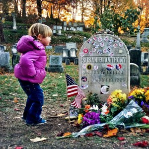 Lizzie Homemaker's young daughter at the grave site of suffrage icon Susan B. Anthony in Mount Hope Cemetery in Rochester shortly after the 2016 presidential election. I voted stickers were left on tombstone.