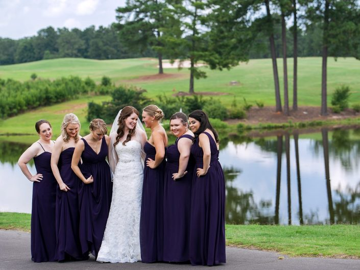 A bride stands with her bridesmaids on a green golf course in NC.