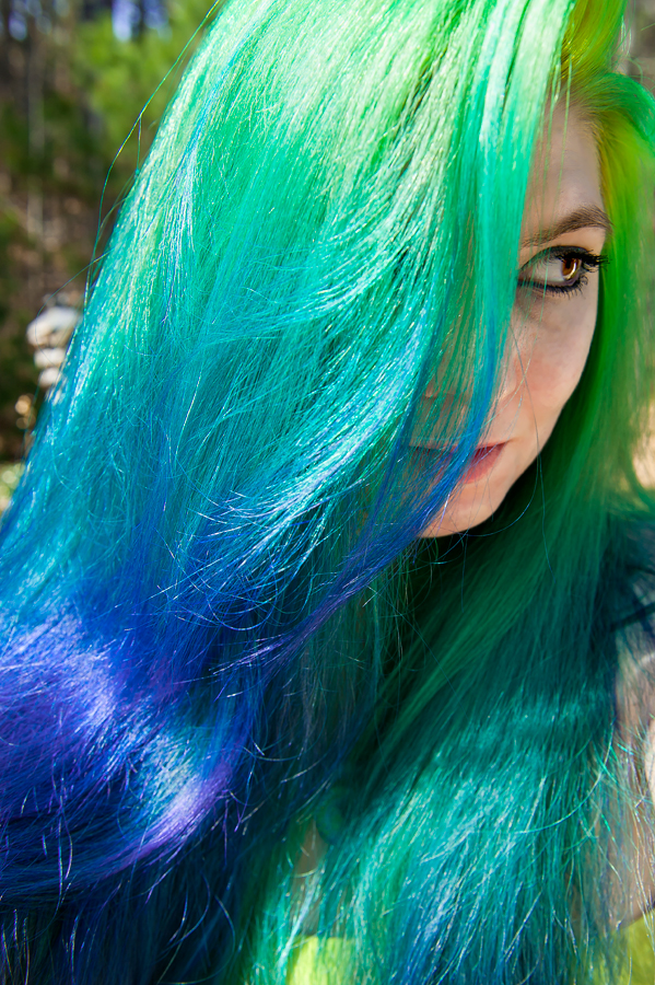 Long colorful hair dyed from a green to blue to purple gradient.