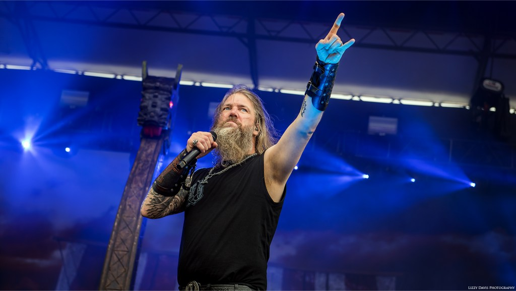 Johan Hegg throws up metal horns to the crowd at Carolina Rebellion.