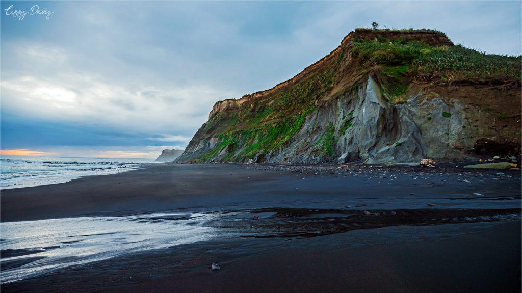 Cliffs and black sand at Waihi Beach. | NZ Travel Photos by Lizzy Davis.