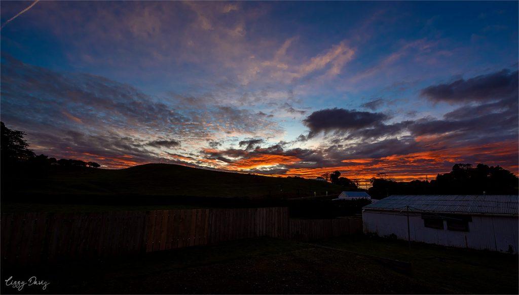 Red sky sunrise in Taranaki, New Zealand. Photo by Lizzy Davis.