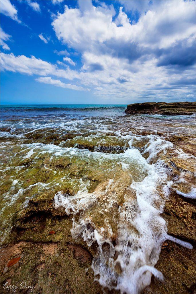 Water crashing over rocks on Paradise Beach, Barbados.