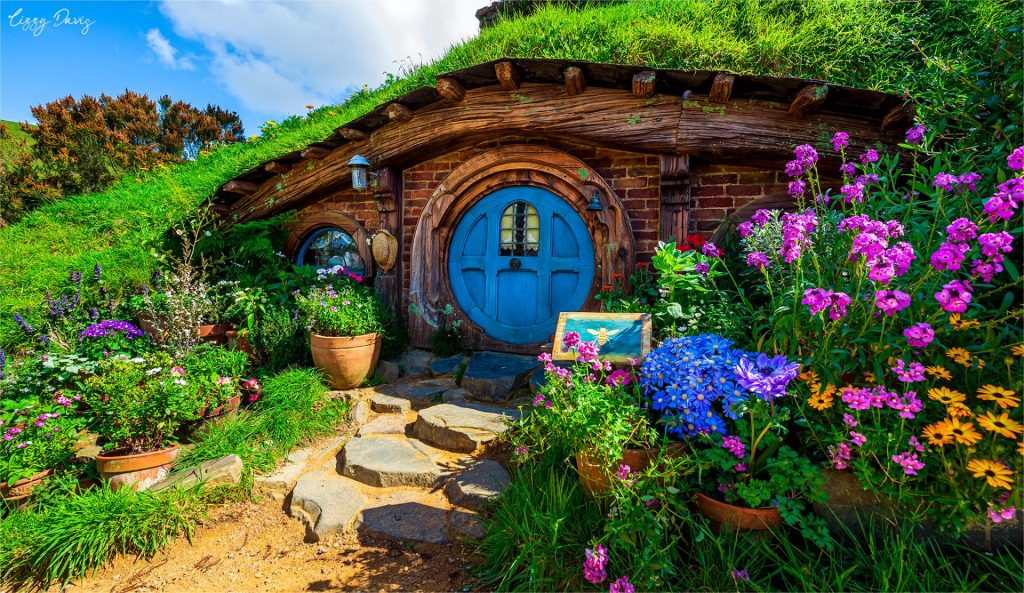 Beautiful brick hobbit hole with a blue door and vibrant colored flowers.