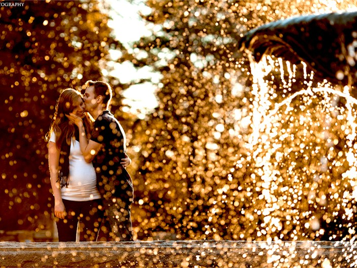 Portrait of a young expecting mother and father in front of a fountain at sunset.