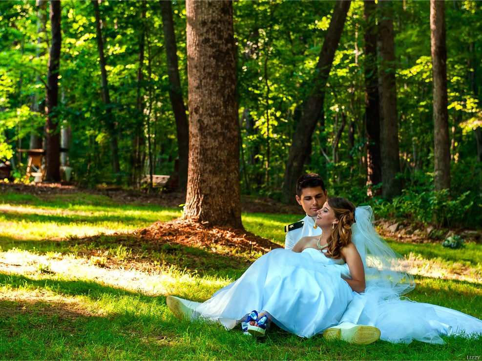 Touching moment between two newlyweds as they sit on the ground.