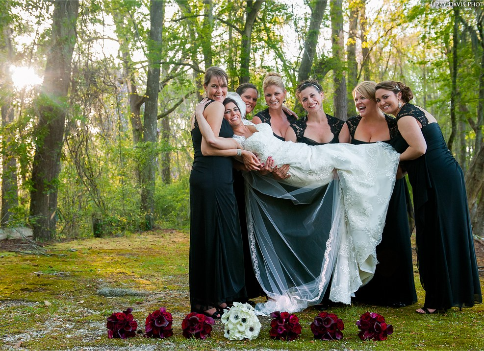 Fun loving bridesmaids proudly carrying the bride against an enchanted forest background. Wedding photography by Lizzy Davis.