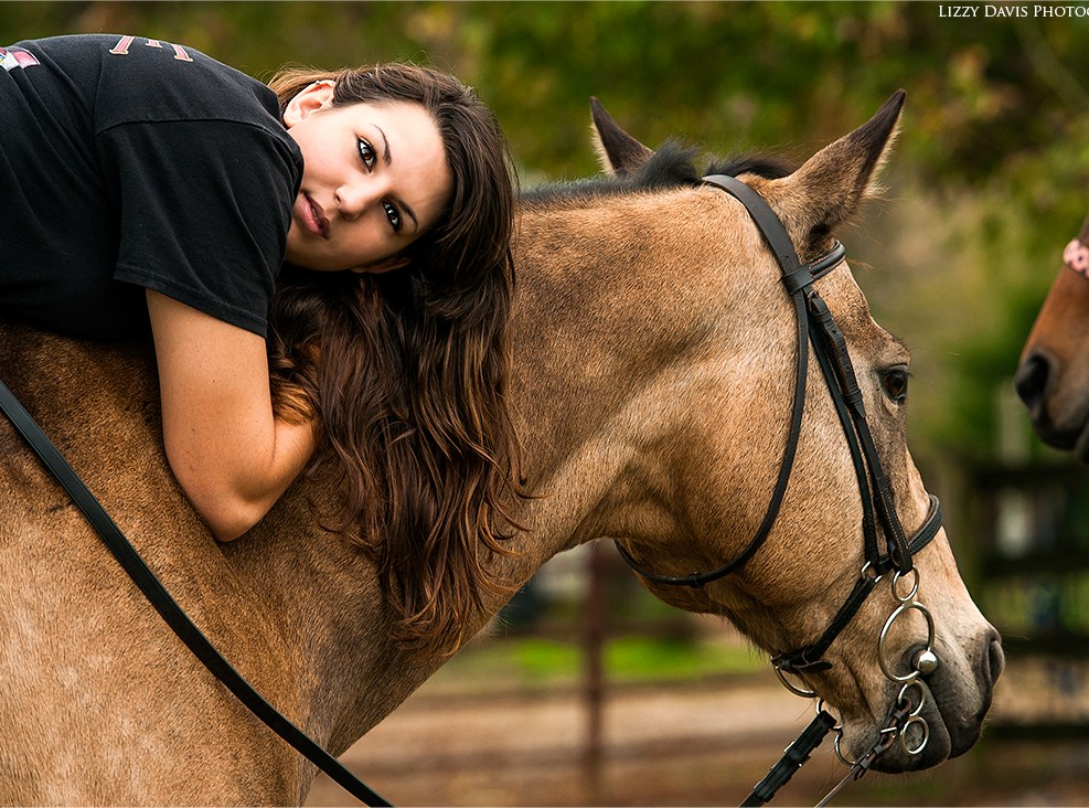 Captivating photo of a young girl laying on her horse.