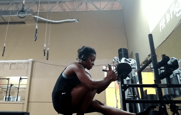 woman doing pistol squat with kettlebell
