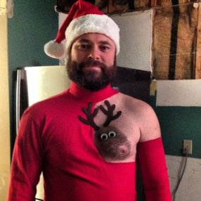 Hairy-chested man shaved chest to look like a reindeer. Nipple is the nose.