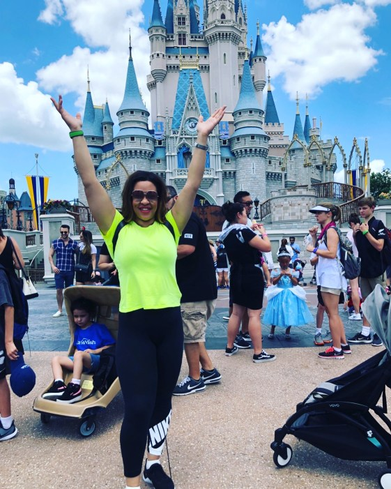 Photo of LMS in a neon yellow top and Nike tights, hands raised in front of Cinderella castle at DisneyWorld.