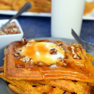 4 pumpkin waffles layered on a blue plate topped with whipped cream, pecans, and syrup with a glass of milk in the background