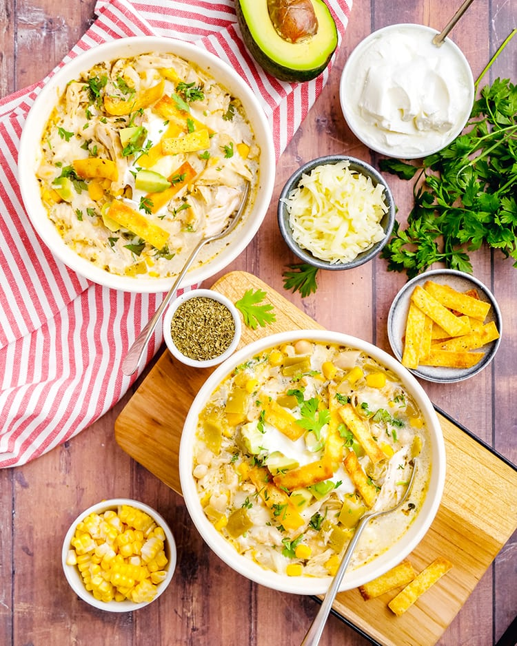 Two bowls of white chicken chili surrounded by little bowls of tortilla strips, cheese, and sour cream.