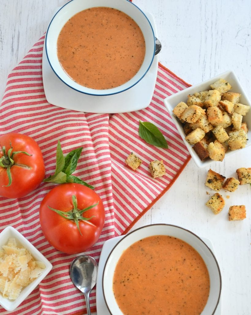 2 bowls of tomato basil so, framed with Parmesan cheese, 2 tomatoes, spoons, bread crumbs on a red and white napkin