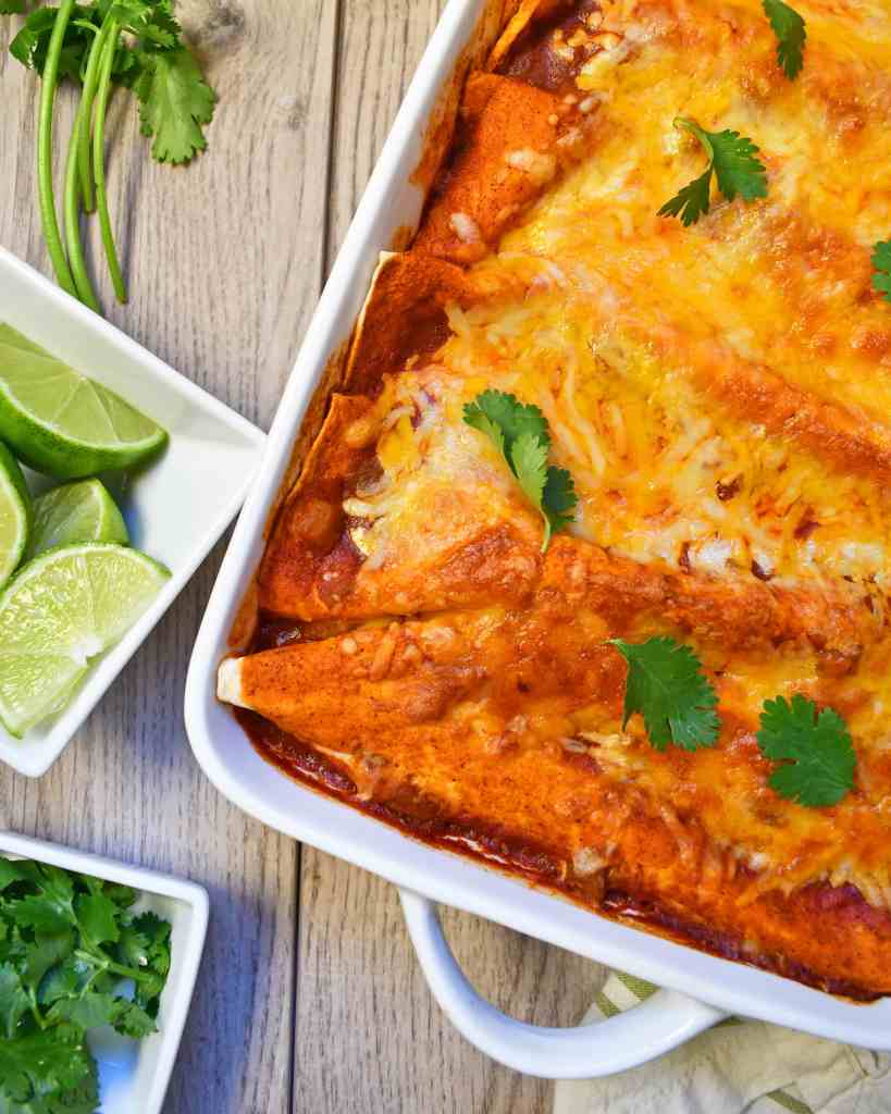 Tender pork simmered in a spicy broth topped with red enchilada sauce and shredded cheese all coming together for simply delicious slow cooker pork enchiladas.