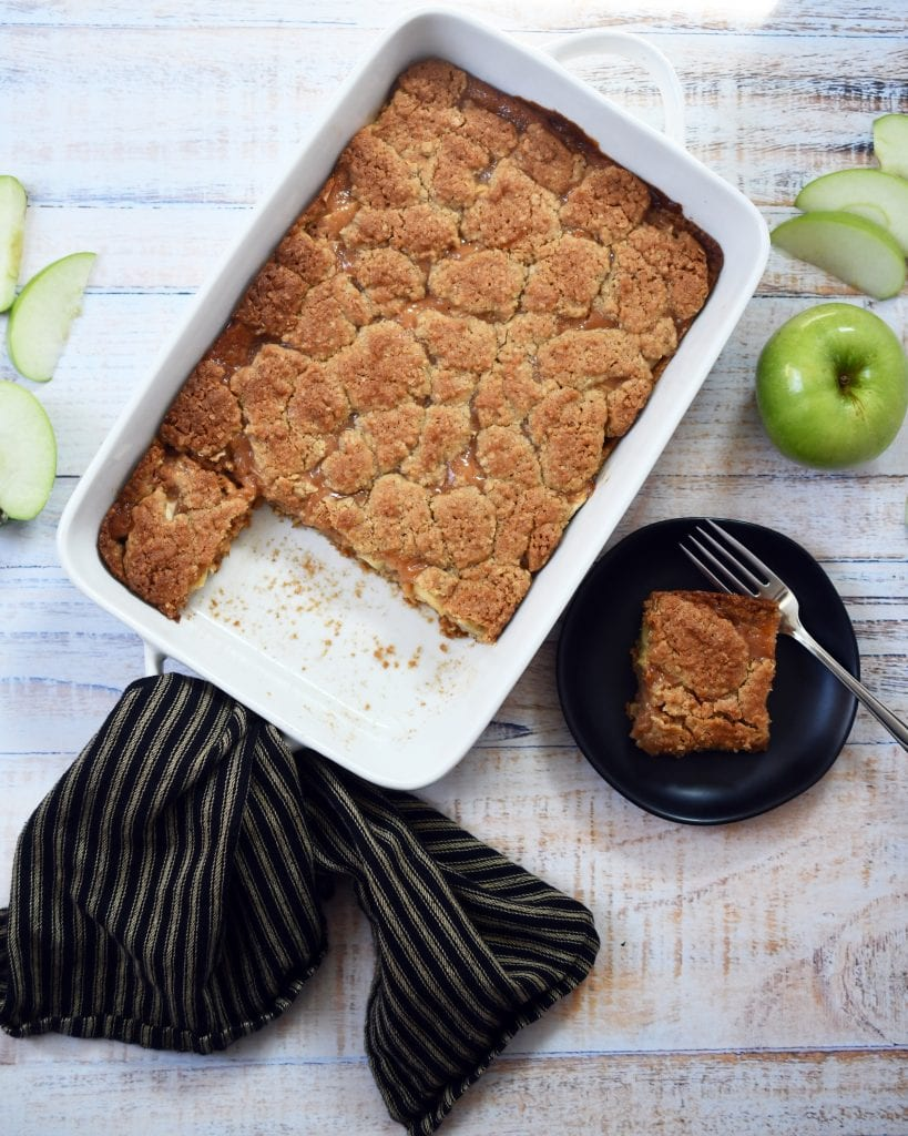 One pan of caramel apple bars in a white baking pan with brown striped napkin, green apple, green apple slices, 1 square of bar on a brown plate with fork