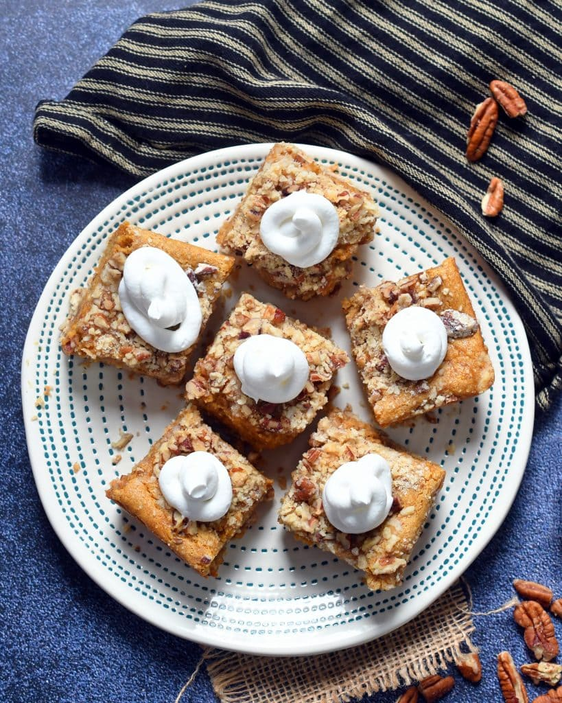 Six pecan pumpkin cheesecake bars topped with whipped cream on a tan plate next to a brown cloth