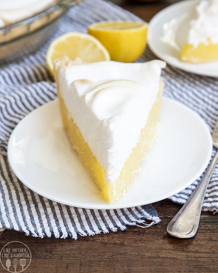 A slice of lemon meringue pie on a white plate, the bottom half is a yellow lemony curd filling topped with a thick white meringue topping.