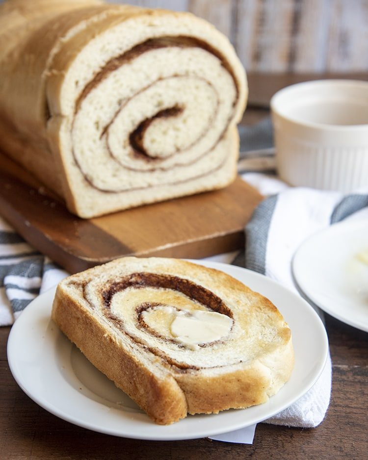 A slice of cinnamon swirl bread with butter on a white plate