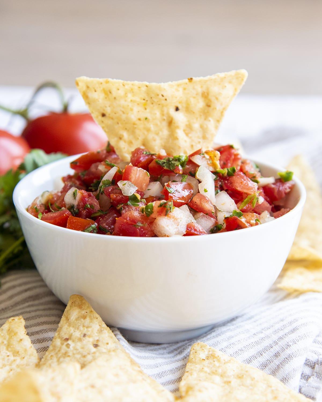 A tortilla chip sticking out of a bowl of homemade salsa.